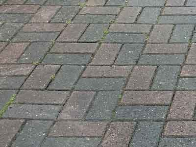 Dirty pavers in need of pressure washing.