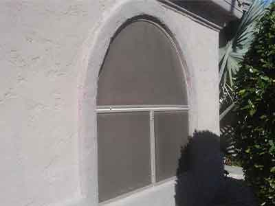 Brown sun screen panels with arched window. Residential window cleaning.