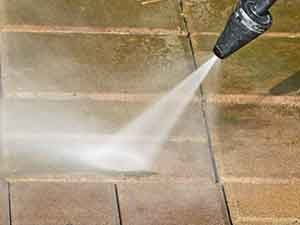 Close up view of pressure washer nozzle cleaning pavers.