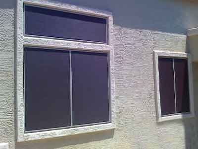 Brown sun screens installed on three windows.