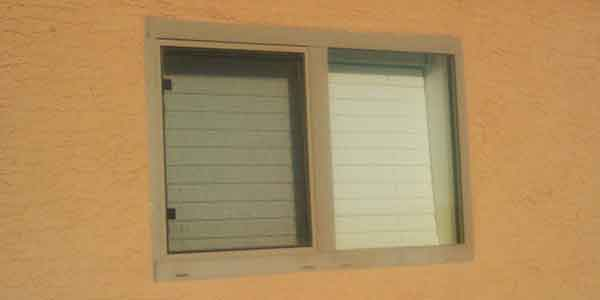 A small slider bathroom window with a bug screen.