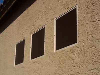 Brown sun screens on picture windows.