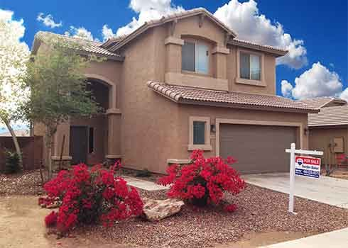 A two story home in Laveen for sale with a Remax sign in the front. Residential window cleaning.