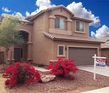 A two story home in Laveen for sale with a Remax sign in the front.